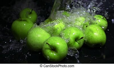 Spilling water over green apples super slow motion shot