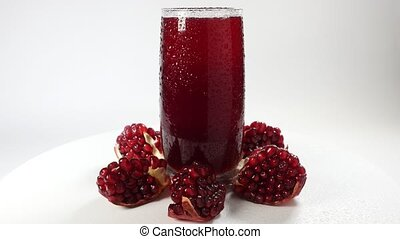 Rotating fresh pomegranate juice with pomegranate segments...