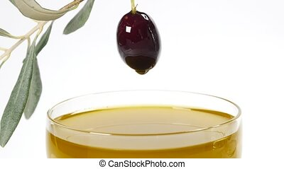 A drop of olive oil falling from one black olive in piala...