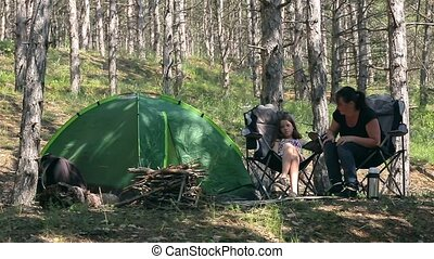 family in the woods with a tent - Mother and daughter sit on...