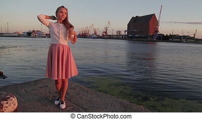 woman brushing her hair and dancing at sunset river port...