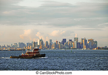 Ferry crossing in front on New York City Manhattan skyline sunset viewed from the bay