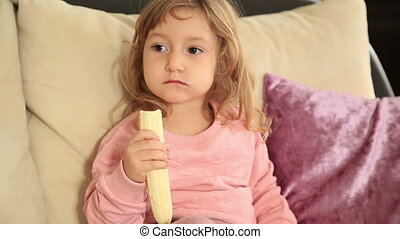 Cute little girl eating eating a banana - Portrait of a two...