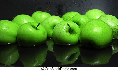 Green apples in water against black background 4K shot