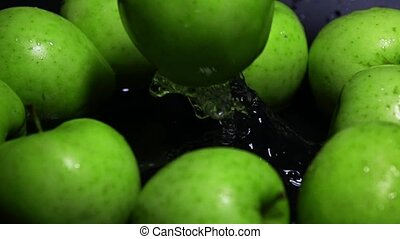 Green apple falling in water super slow motion shot