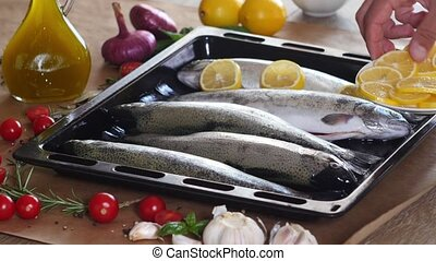 the chef prepares a trout for baking in the oven, lays out...