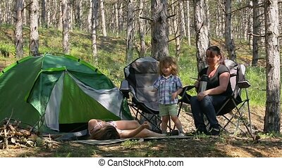 Mother and son played on a blanket in the woods. Little cute boy with his mother to spend time in nature at the campsite.