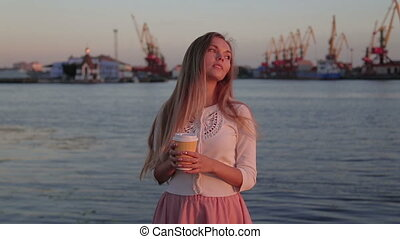 woman drink cofee watching at sunset river port
