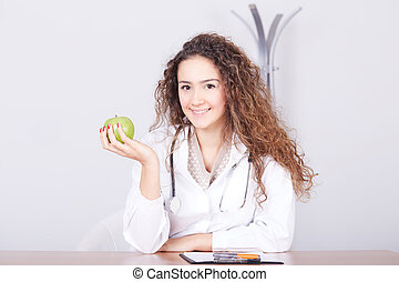woman doctor with a green apple.