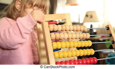 Cute little girl playing with abacus - Two years old kid...