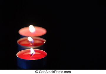Some burning candles in the dark close up