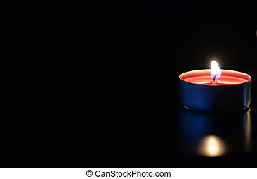 A burning candle in the dark close up