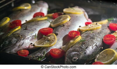 delicious trout fish is baking in the oven with lemon, tomatoes and spices