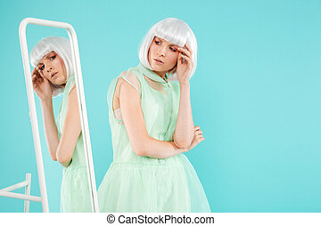 Woman in blonde wig standing and posing near the mirror -...