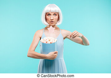 Pretty young woman with marshmallows standing and using...