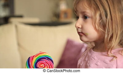 Cute little girl with candy watching tv - Portrait of a cute...