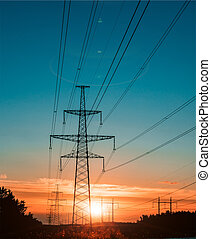electricity transmission pylon at city suburb against the sunset glow sky.