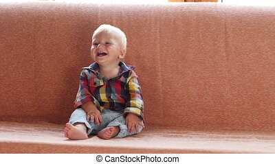 little cute child sitting on a couch and laughing - little...
