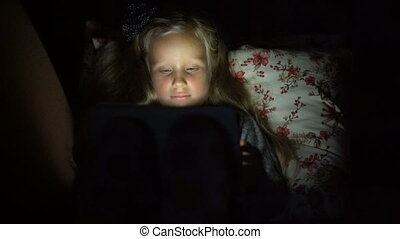 five year old girl looking cartoon lying on the couch in the...