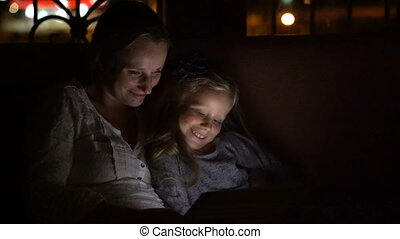 Mom and daughter at dusk looks hilarious film on a tablet
