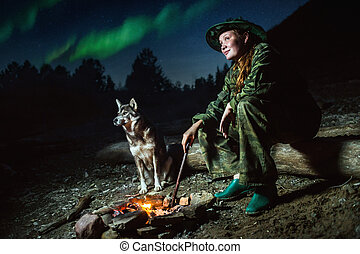 Scout girl with her dog around campfire at night stars and...