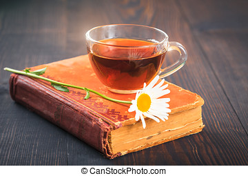 Cup of tea, chamomile and a book on the table - Cup of tea,...