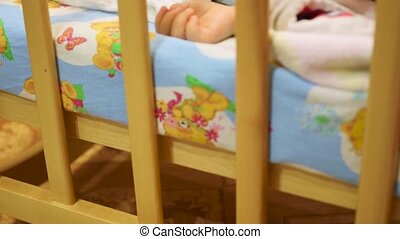 the sweet baby sleeps in a cot with a teddy bear - the baby...