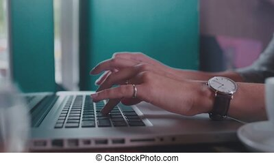 Close up. Female hand with a wristwatch typing on a laptop...