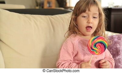 Funny little girl with long, curly hair holding big colorful Lollipop