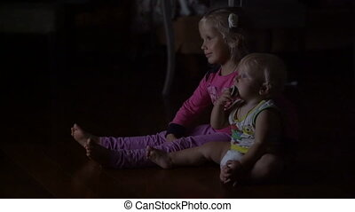 little brother with his sister watching television sitting in the dark