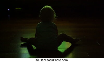 little kid watching television sitting on the floor at dusk