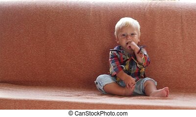 little cute child sitting on a couch at home