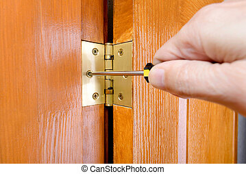 Adjusting a Door Hinge - A man is using a screwdriver to...