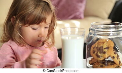 Little cute girl eating cookie and drining milk - Portrait...