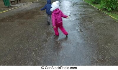 Boy and girl go on a wet road. Children run through the...