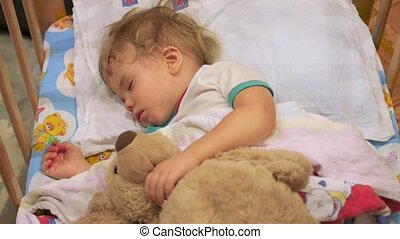 the sweet baby sleeps in a cot with a teddy bear.