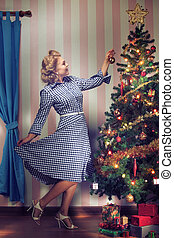 x-mas tree and girl - portrait of nice young woman hanging...