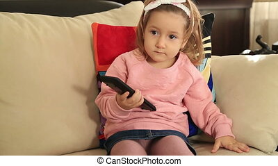 Little girl watching television - Portrait of a cute child...