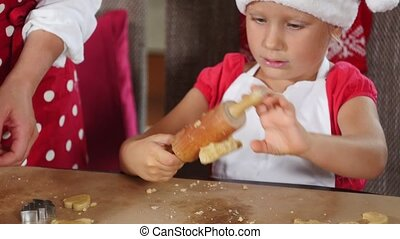 Mother and daughter are preparing gingerbread for Christmas...