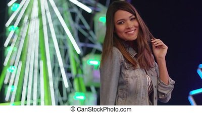 Pretty happy young woman relaxing at a funfair posing in...