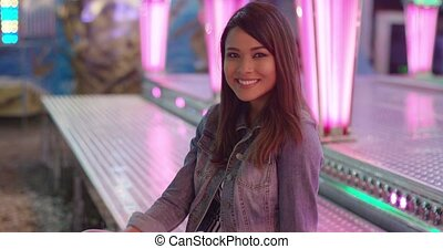 Sexy young woman enjoying a night out at a colorful funfair...