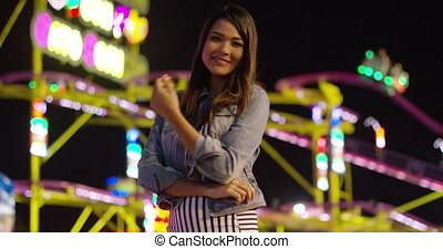 Vivacious young woman at an evening funfair standing...