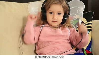 Portrait of a cute little girl listening to music - A little...