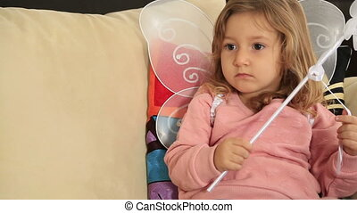 Portrait of a cute little girl with angel wing watching tv...