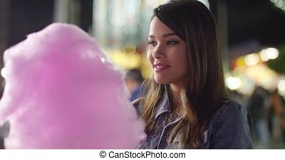 Laughing young woman eating pink candy floss pulling of a...