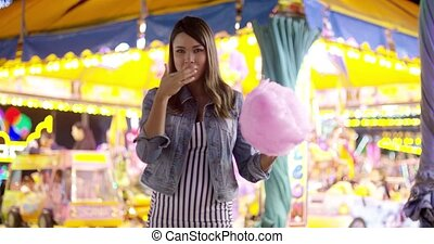 Young woman having fun at a colorful fairground standing...