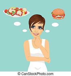 young woman choosing between hamburger and salad. Healthy...