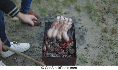 Barbecue browned sausages on the hot grill, a person turn...