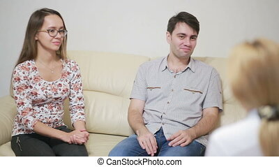 Female psychologist helping worried young couple. family...