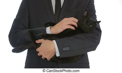 businessman holding a black cat in her arms - male...